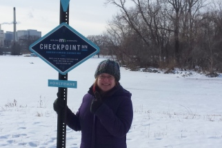 a woman in a purple coat holding onto a blue Checkpoint sign, giving a thumbs-up sign with her other hand