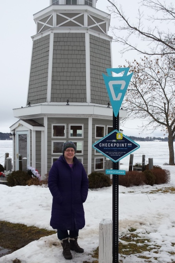 a woman in a purple coat standing next to a blue sign in front of a gray windmill