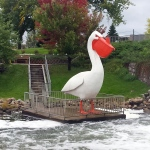 large pelican statue standing on a wide dock over a river