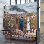 mural of about 30 people from the war, with a dark smoke plume and destruction in the background