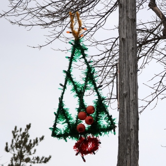 Green tinsel tree with a gold diamond at the top and a red base