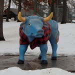 blue ox wearing a red-and-black plaid short-sleeved shirt