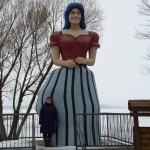 a woman standing next to a very tall statue of a woman in a red shirt and blue-and-black striped dress