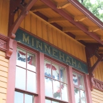 angled view of a yellow building with maroon trim, and the word MINNEHAHA above a window