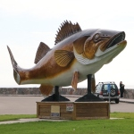 large fish statue with its tail curved, mounted on two poles