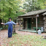 a man in overalls gesturing in front of a log cabin