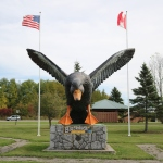 Large black duck statue that appears to be swooping toward the camera