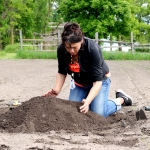 a kneeling woman building a mound of dirt with her hands
