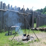 cast-iron pot hanging over a small fire, with a table nearby, a tall wooden fence in the background