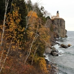 popple trees with a few yellow leaves remaining next to a rocky coast, a light-brown lighthouse on a tall cliff in the background