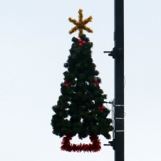 Greenery tree, almost completely filled in, with a gold tinsel star and red tinsel trunk