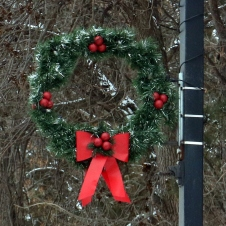 Greenery wreath with four sets of three red berries, no candles in the center