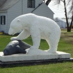 a polar bear statue with its paw on a seal